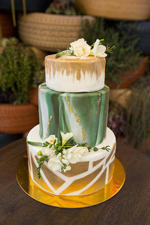 lot-8-cake-three-teirs-gold-and-green-with-geometirc-pattern-on-the-bottom-layer-and-white-flowers-adorning-the-top