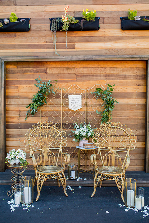 lot-8-chairs-wooden-boho-style-chairs-with-rounded-almost-wicker-like-top-in-a-carmel-brown-color-with-greenery-and-white-candles-all-around-and-reclaimed-wood-wall