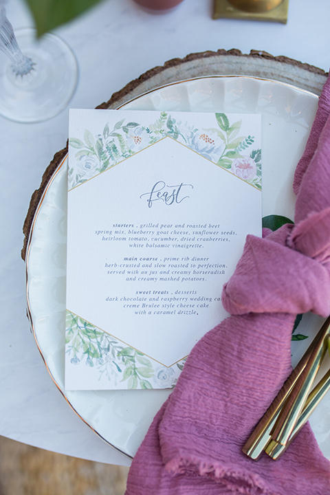 lot-8-close-up-on-plates-and-napkins-rose-colored-linnen-nakins-with-menu-card-in-white-with-floral-embellishments-and-pastel-calligraphy