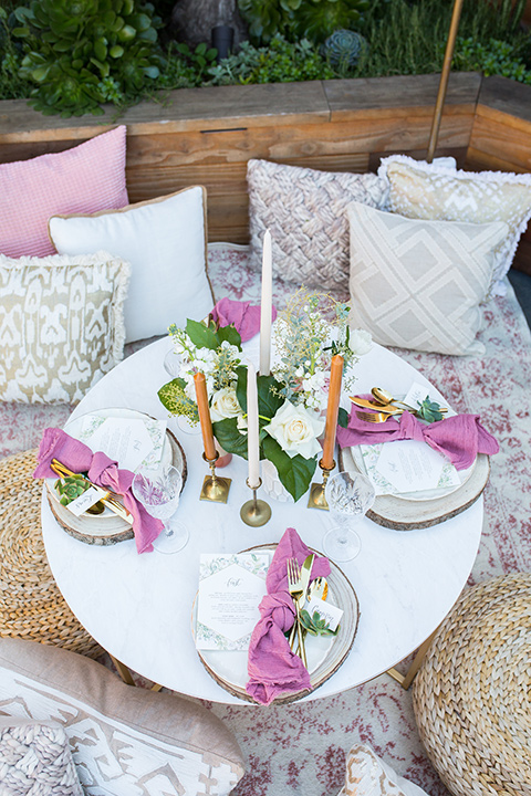 lot-8-table-set-up-with-pillows-rose-colored-napkins-with-white-table-and-white-plates-with-gold-accents