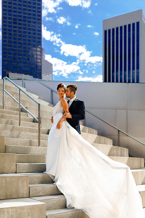 Downtown-los-angeles-wedding-shoot-at-oue-skyspace-bride-and-groom-hugging-on-stairs