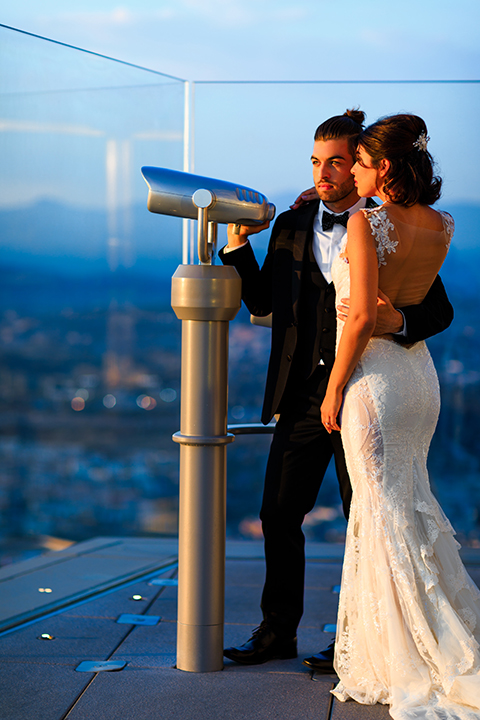 Downtown-los-angeles-wedding-shoot-at-oue-skyspace-bride-and-groom-standing-by-telescope