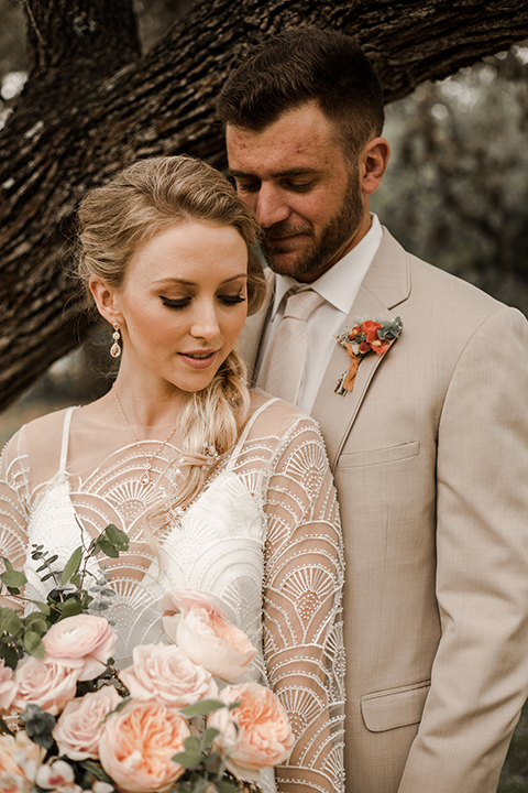 Texas-peaches-and-cream-wedding-shoot-at-carola-horse-ranch-bride-and-groom-hugging-close-up
