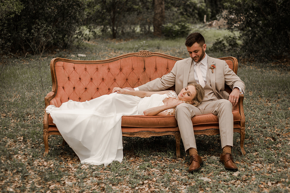 Texas-peaches-and-cream-wedding-shoot-at-carola-horse-ranch-bride-and-groom-sitting-on-couch-smiling