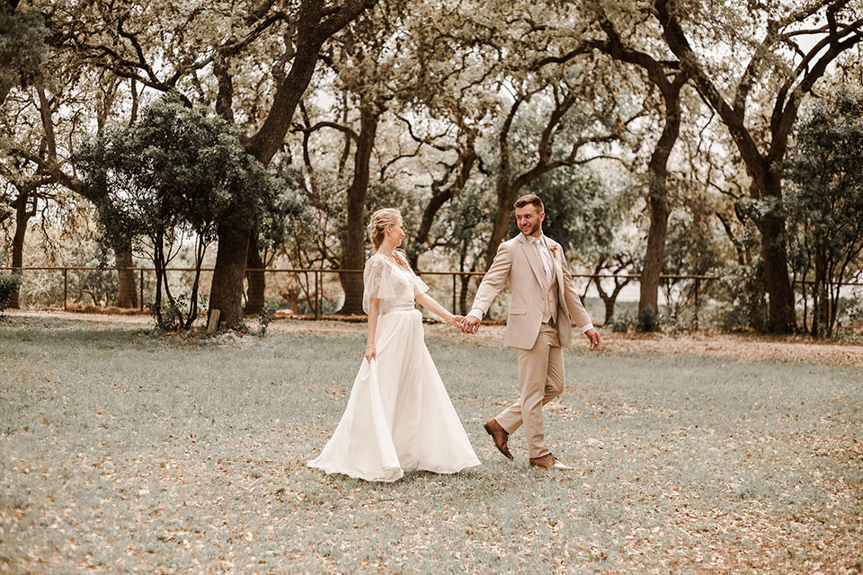 Texas-peaches-and-cream-wedding-shoot-at-carola-horse-ranch-bride-and-groom-standing-holding-hands