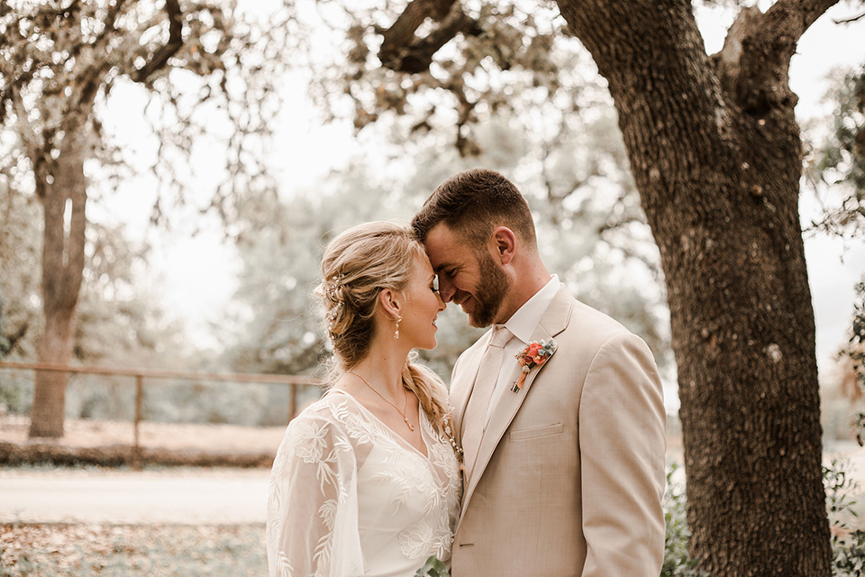 Texas-peaches-and-cream-wedding-shoot-at-carola-horse-ranch-bride-and-groom-standing-hugging