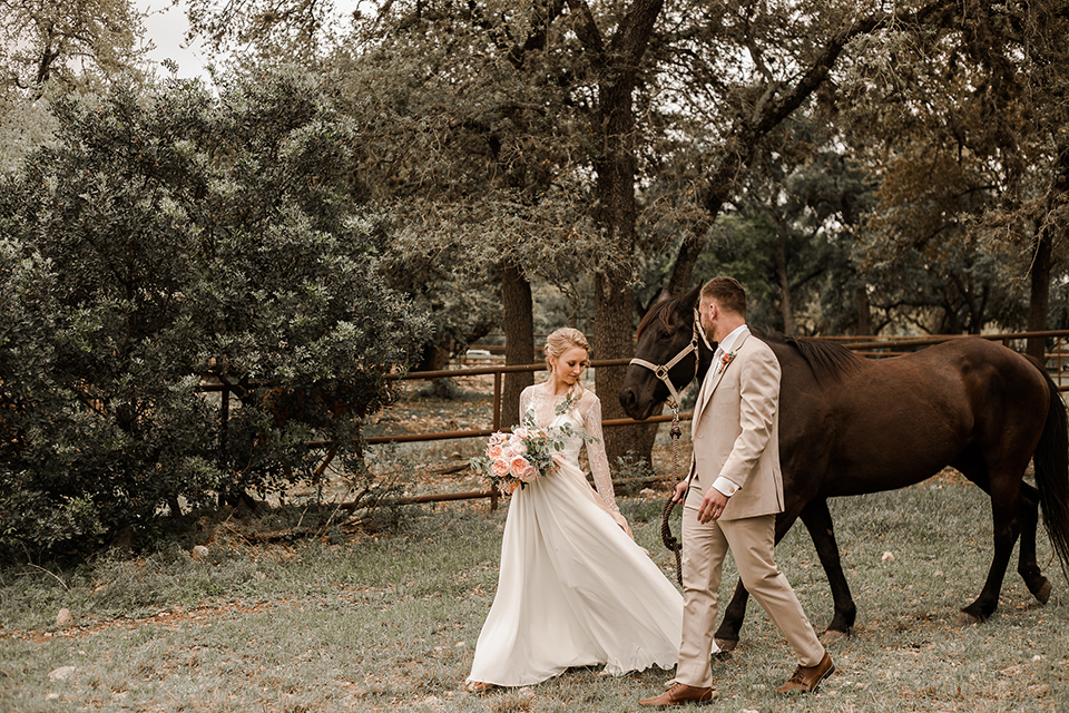 Texas-peaches-and-cream-wedding-shoot-at-carola-horse-ranch-bride-and-groom-walking-with-horse