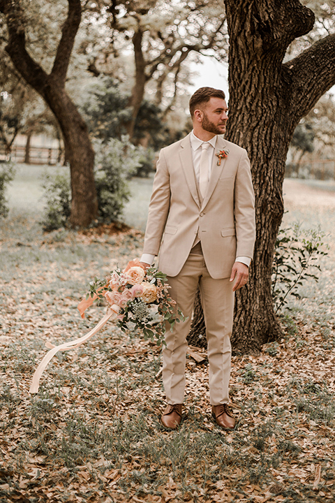 Texas-peaches-and-cream-wedding-shoot-at-carola-horse-ranch-groom-holding-bouquet