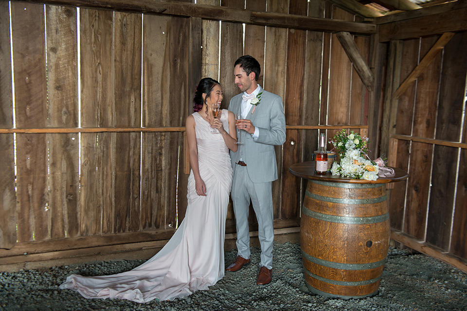 temperino-ranch-wedding-bride-and-groom-in-barn-with-champgaine-bide-back-turned-bride-in-a-lace-dress-with-straps-and-hair-pulled-back-groom-in-a-light-grey-suit