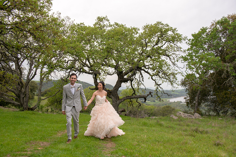 temperino-ranch-wedding-bride-and-groom-walking-in-tree-area-bide-back-turned-bride-in-a-lace-dress-with-straps-and-hair-pulled-back-groom-in-a-light-grey-suit