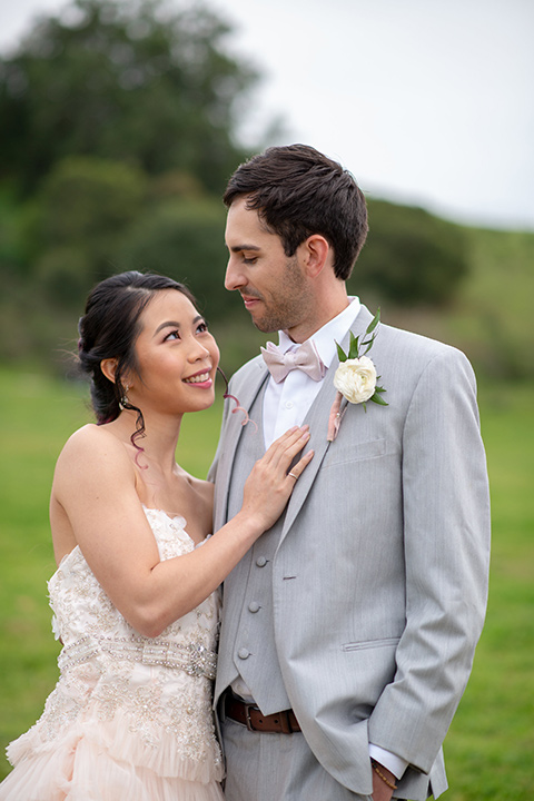 temperino-ranch-wedding-bride-and-groom-bride-in-a-lace-dress-with-straps-and-hair-pulled-back-groom-in-a-light-grey-suit