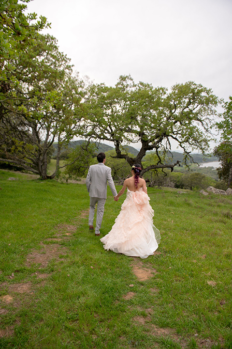 temperino-ranch-wedding-couple-walking-away-from-camera-bride-in-a-lace-dress-with-straps-and-hair-pulled-back-groom-in-a-light-grey-suit