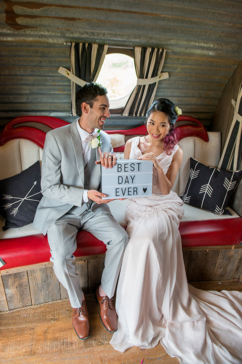 temperino-ranch-wedding-photobooth-inside-bride-in-a-lace-dress-with-straps-and-hair-pulled-back-groom-in-a-light-grey-suit