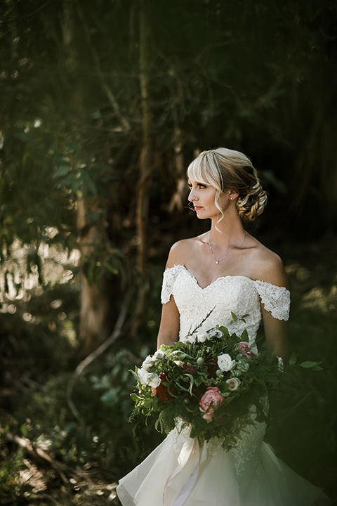 saddle-peak-bride-alone-bride-in-an-off-the-shoulder-gown-with-lace-detailing-and-hair-up-in-a-bun