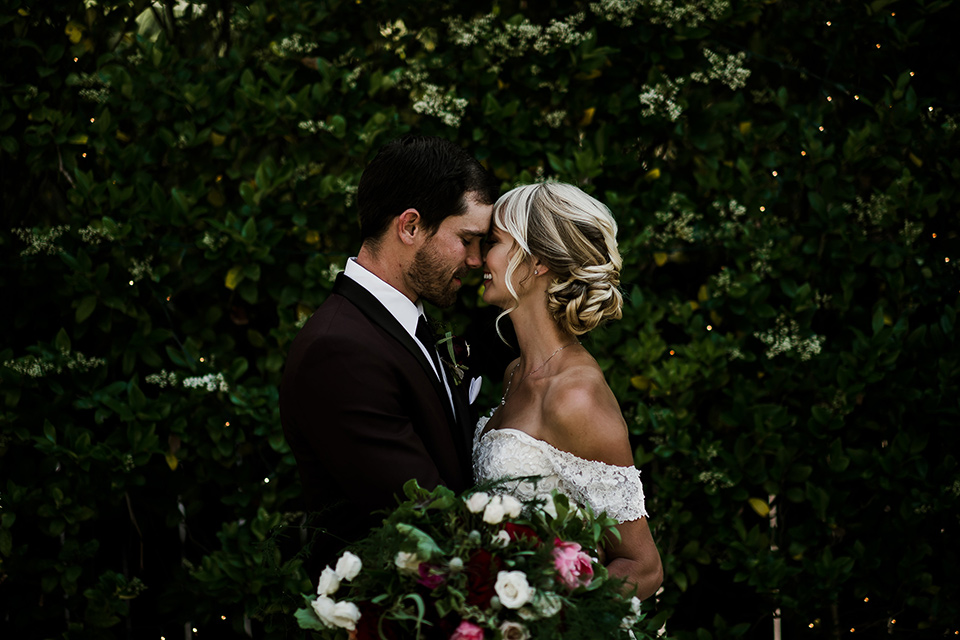 saddle-peak-bride-and-groom-at-ceremony-space-bride-in-an-off-the-shoulder-gown-with-lace-detailing-and-hair-up-in-a-bun-groom-in-a-burgundy-tuxedo-with-a-long-tie