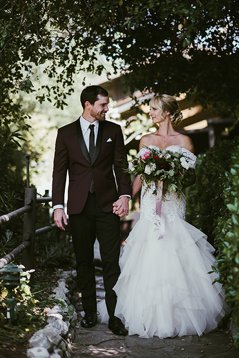 saddle-peak-bride-and-groom-looking-at-eachother-and-walking-bride-in-an-off-the-shoulder-gown-with-lace-detailing-and-hair-up-in-a-bun-groom-in-a-burgundy-tuxedo-with-a-long-tie