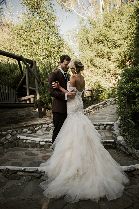 saddle-peak-bride-and-groom-on-steps-bride-in-an-off-the-shoulder-gown-with-lace-detailing-and-hair-up-in-a-bun-groom-in-a-burgundy-tuxedo-with-a-long-tie