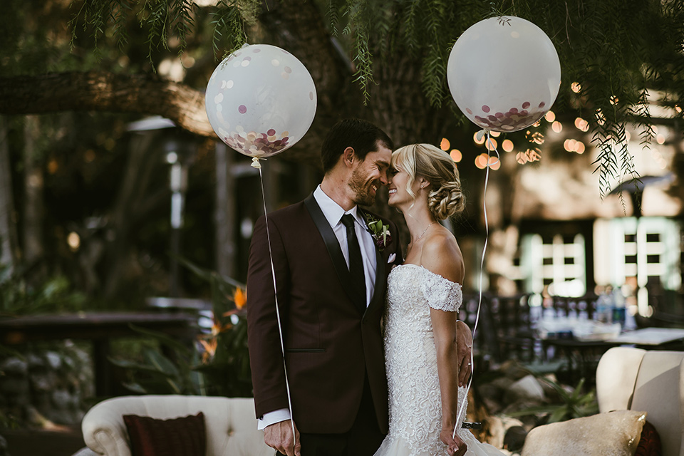 saddle-peak-bride-and-groom-with-balloons-bride-in-an-off-the-shoulder-gown-with-lace-detailing-and-hair-up-in-a-bun-groom-in-a-burgundy-tuxedo-with-a-long-tie