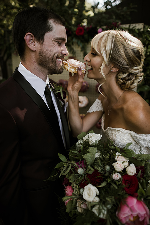 saddle-peak-bride-and-groom-with-donuts-bride-in-an-off-the-shoulder-gown-with-lace-detailing-and-hair-up-in-a-bun-groom-in-a-burgundy-tuxedo-with-a-long-tie