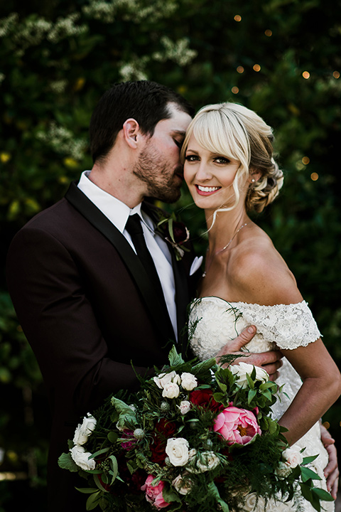 saddle-peak-bride-looking-at-camera-groom-looking-at-her-bride-in-an-off-the-shoulder-gown-with-lace-detailing-and-hair-up-in-a-bun-groom-in-a-burgundy-tuxedo-with-a-long-tie