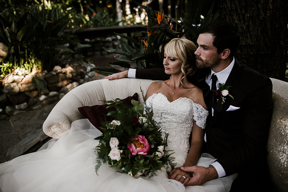 saddle-peak-couple-on-couch-bride-in-an-off-the-shoulder-gown-with-lace-detailing-and-hair-up-in-a-bun-groom-in-a-burgundy-tuxedo-with-a-long-tie