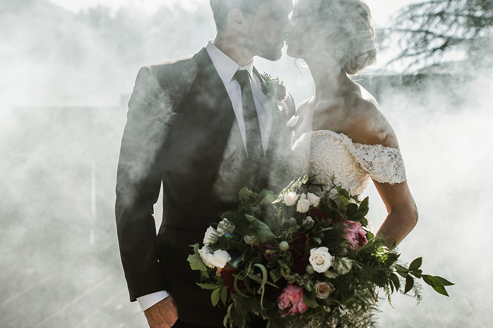 saddle-peak-shoot-bride-and-groom-close-up-in-smoke-bride-in-an-off-the-shoulder-gown-with-lace-detailing-and-hair-up-in-a-bun-groom-in-a-burgundy-tuxedo-with-a-long-tie