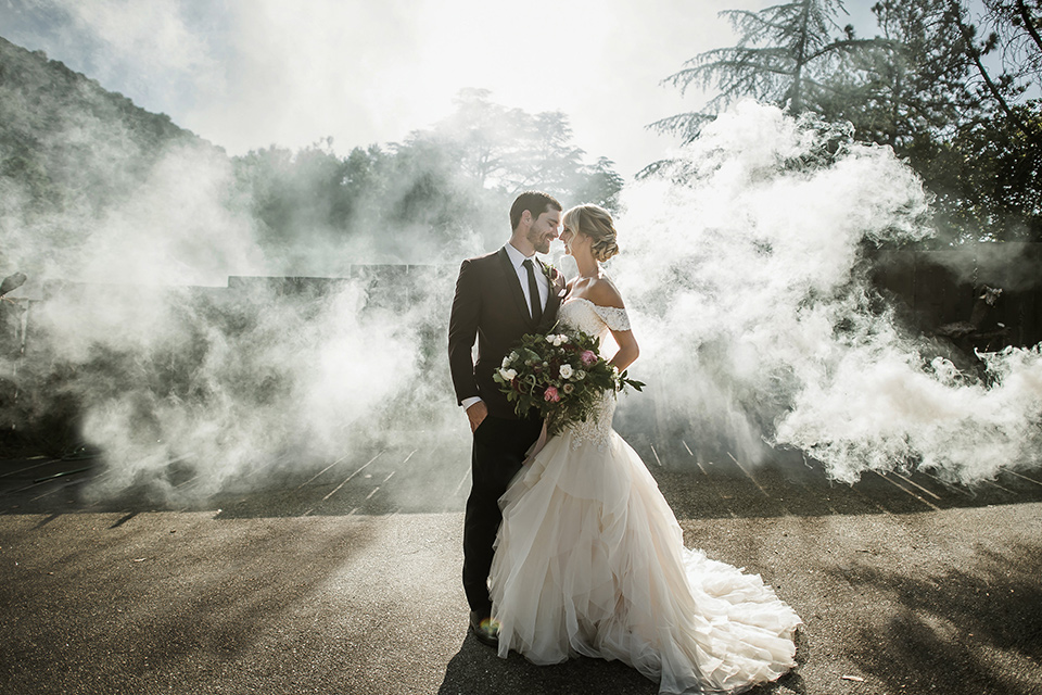 saddle-peak-shoot-bride-and-groom-with-smoke-behind-them-bride-in-an-off-the-shoulder-gown-with-lace-detailing-and-hair-up-in-a-bun-groom-in-a-burgundy-tuxedo-with-a-long-tie