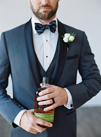 Same-sex-industrial-wedding-at-the-1912-groom-charcoal-tuxedo-close-up-holding-drink