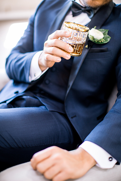 Same-sex-industrial-wedding-at-the-1912-groom-navy-tuxedo-close-up-holding-glass