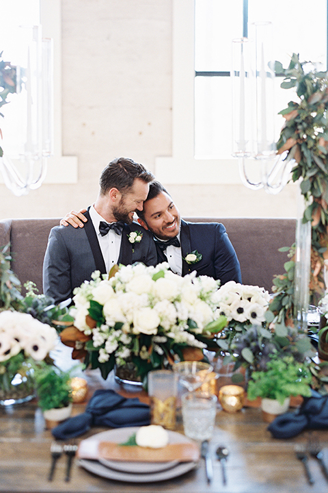 Same-sex-industrial-wedding-at-the-1912-grooms-sitting-at-table-hugging
