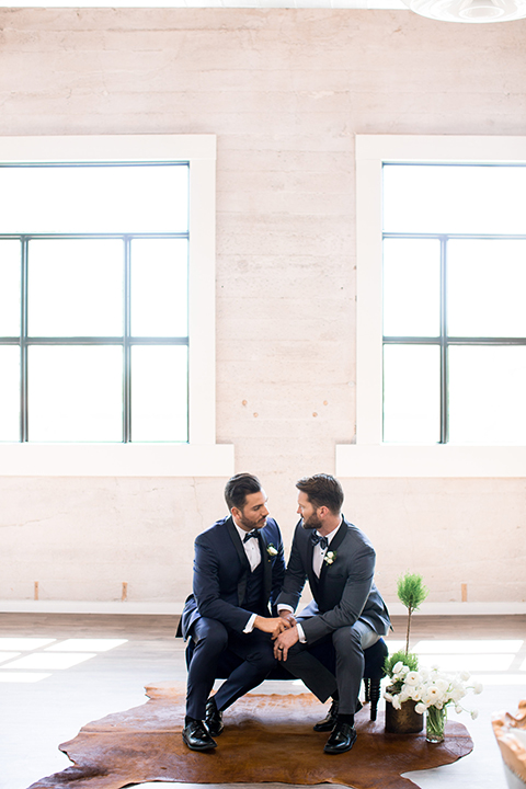 Same-sex-industrial-wedding-at-the-1912-grooms-sitting-holding-hands