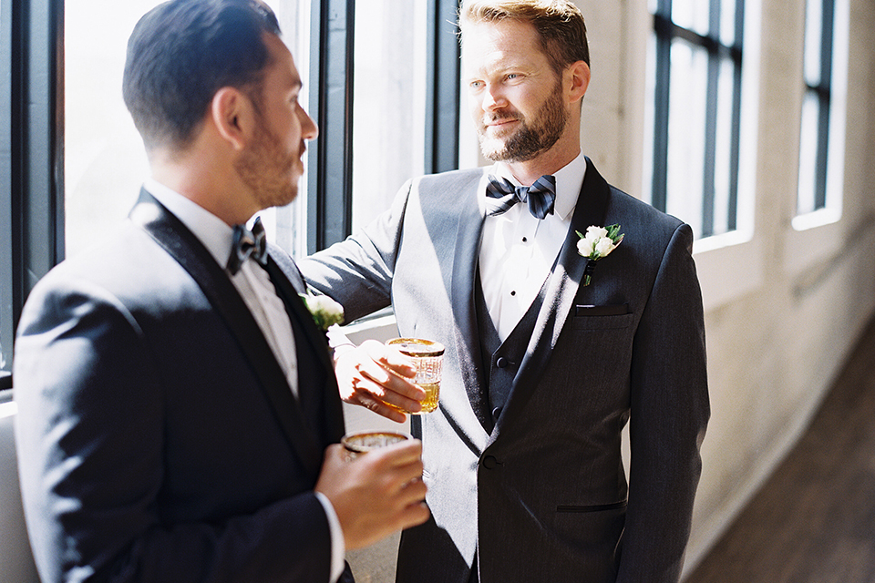 Same-sex-industrial-wedding-at-the-1912-grooms-standing-and-smiling-holding-drinks