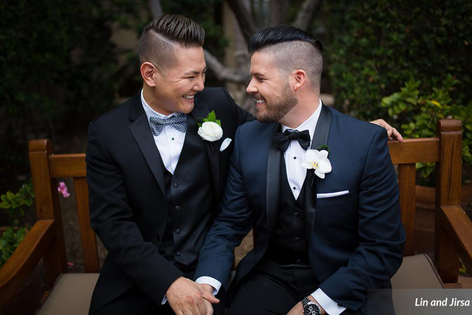 Laguna-beach-outdoor-wedding-same-sex-grooms-holding-hands-and-sitting