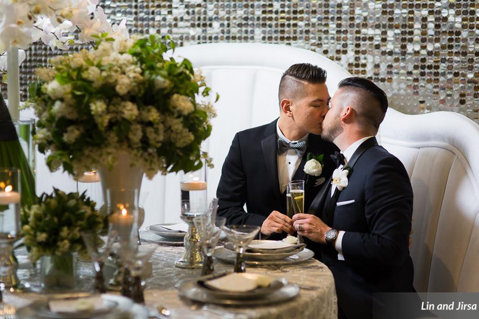 Laguna-beach-outdoor-wedding-same-sex-grooms-sitting-at-table-kissing