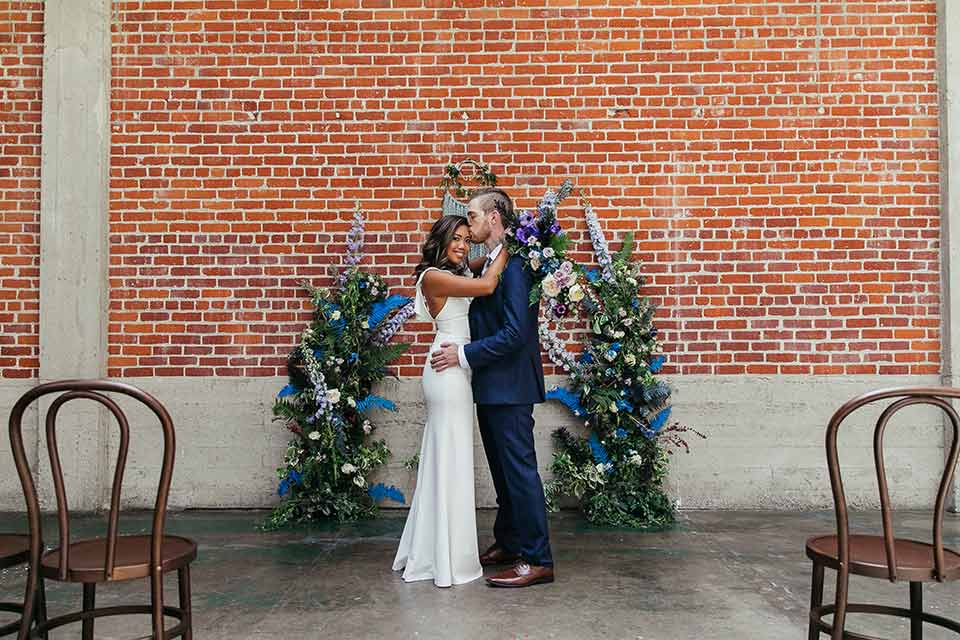 Sandbox-styled-shoot-bride-and-groom-at-altar-groom-kissing-bride-bride-looking-at-camera-brick-wall-behind-them-with-boho-floral-archway-and-wooden-chairs