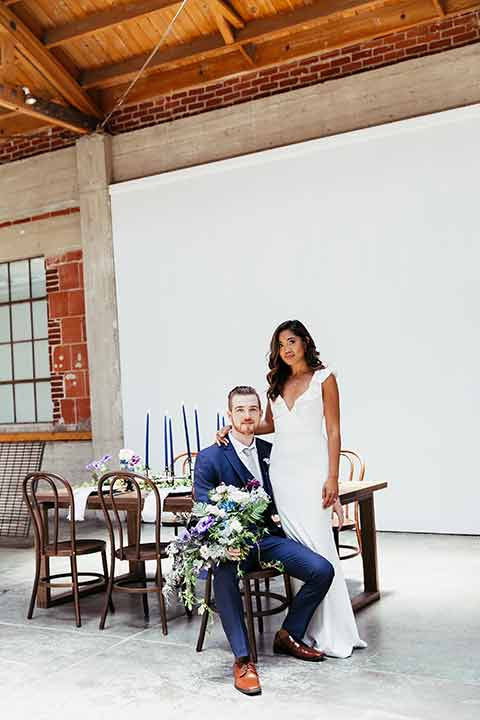 Sandbox-styled-shoot-bride-and-groom-at-table-goom-sitting-in-chair-holding-flowers-bride-in-a-white-dress-with-flutte-sleeves-and-deep-v-neckline-groom-with-navy-suit-and-grey-tie-paired-with-light-brown-shoes
