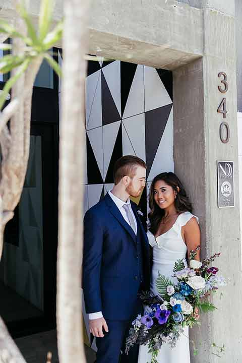Sandbox-styled-shoot-bride-and-groom-by-tiled-wall-groom-looking-atbride-bride-looking-at-camera-bride-in-white-gown-with-flutter-sleeves-and-deep-v-neckline-groom-in-blue-suit-with-floral-bouquet