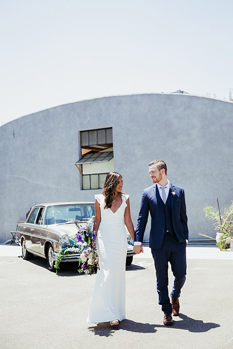 Sandbox-styled-shoot-bride-and-groom-looking-at-each-other-walking-towards-camera-away-from-vintage-car-bride-in-white-gown-with-flutter-sleeves-and-deep-v-neckline-groom-in-blue-suit-and-grey-tie