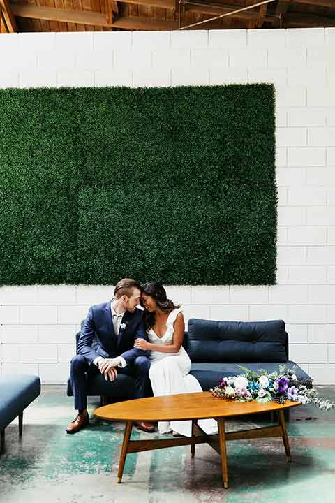 Sandbox-styled-shoot-bride-and-groom-touchng-heads-with-green-background-retro-table-in-front-of-them-bride-in-white-gown-with-flutter-sleeves-and-groom-in-a-blue-suit-with-a-grey-tie