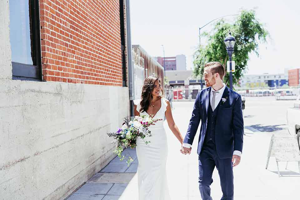 Sandbox-styled-shoot-bride-and-groom-walking-towards-camera-looking-at-each-other-near-brick-wall-outside-bride-wearing-a-white-gown-with-flutter-sleeves-groom-in-blue-suit-with-grey-tie