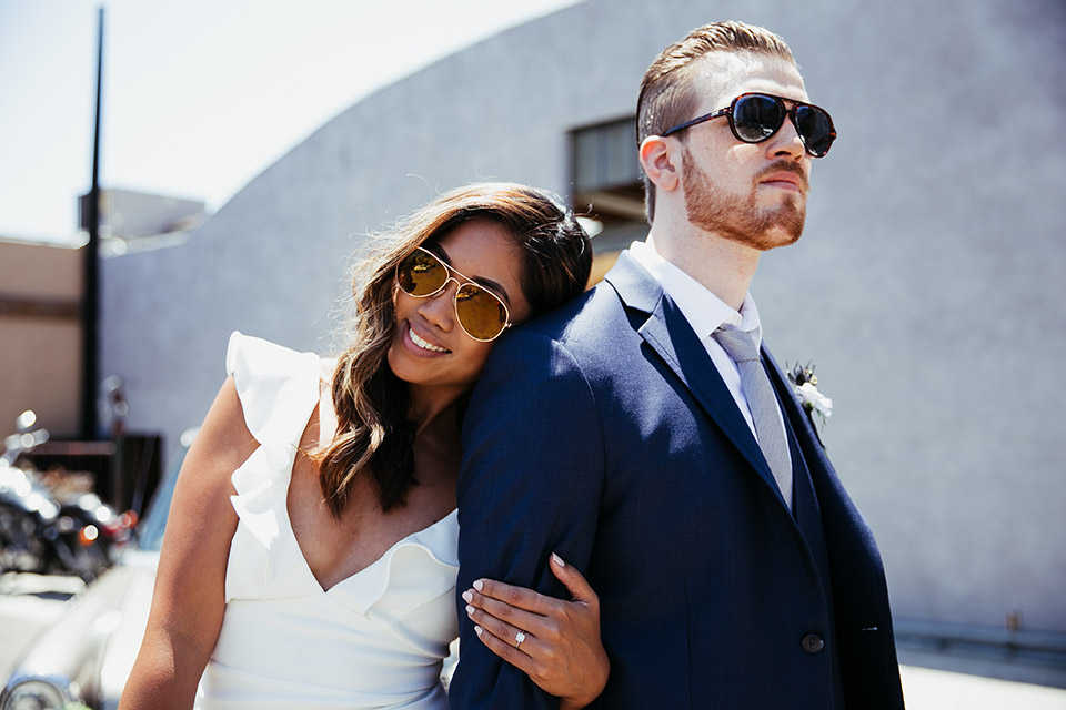 Sandbox-styled-shoot-bride-and-groom-with-sunglasses-in-front-of-vintage-car-bride-wearing-a-white-gown-with-flutter-sleeves-groom-in-blue-suit-with-grey-tie