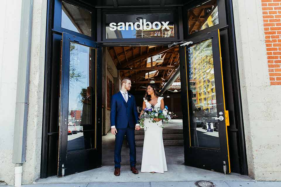 Sandbox-styled-shoot-bride-and-groom-with-venue-logo-behind-them-bride-wearing-a-white-gown-with-flutter-sleeves-groom-in-blue-suit-with-grey-tie
