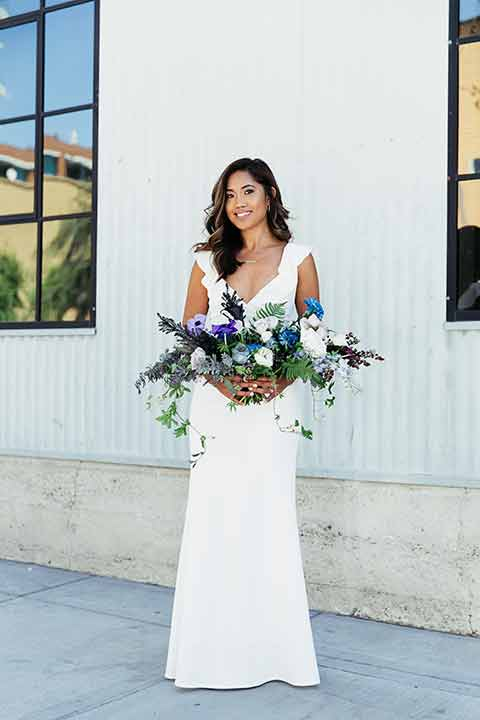 Sandbox-styled-shoot-bride-full-length-gown-with-flutter-sleevvevs-hair-down-holding-bouquet