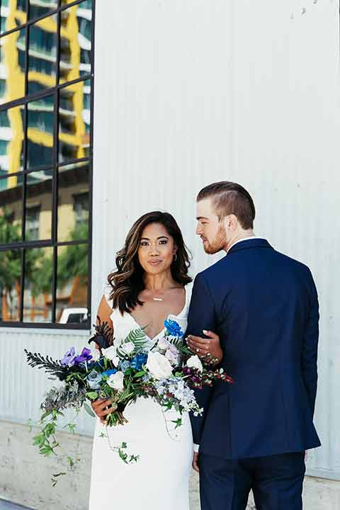 Sandbox-styled-shoot-bride-looking-at-camera-groom-back-turned-away-bride-full-length-gown-with-flutter-sleeves-hair-down-holding-bouquet-groom-in-blue-suit
