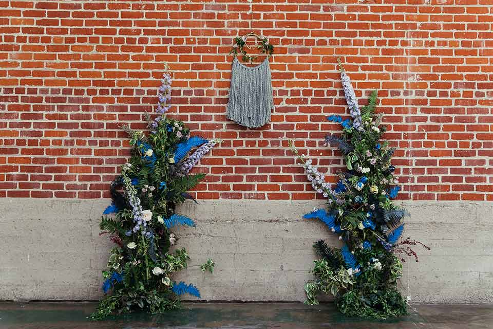Sandbox-styled-shoot-ceremony-atch-arch-has-green-plants-with-blue-floral-accebts-on-brick-wall