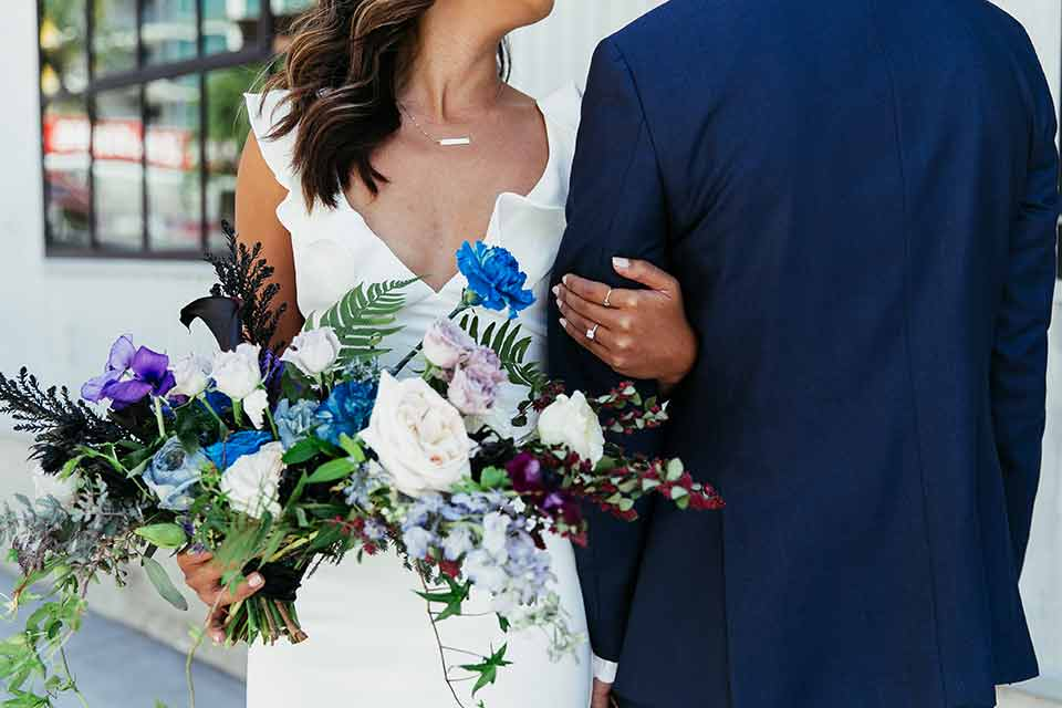 Sandbox-styled-shoot-close-up-on-bridal-bouquet-briide-with-white-dress-and-flutter-sleeves-groom-in-blue-suit-holding-floral-bouquet