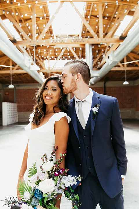 Sandbox-styled-shoot-groo-kissing-brides-head-bride-smiling-at-camera-lights-and-and-brick-behind-them-bride-wearing-a-white-dress-with-flutter-sleeves-groom-wearing-a-blue-suit-and-grey-tie