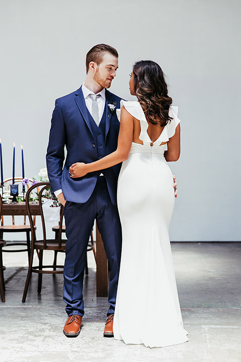 Sandbox-styled-shoot-groom-facing-camera-bride-back-turned-looking-at-each-other-bride-wearing-a-white-dress-with-flutter-sleeves-and-open-back-groom-wearing-a-blue-suit-and-grey-tie