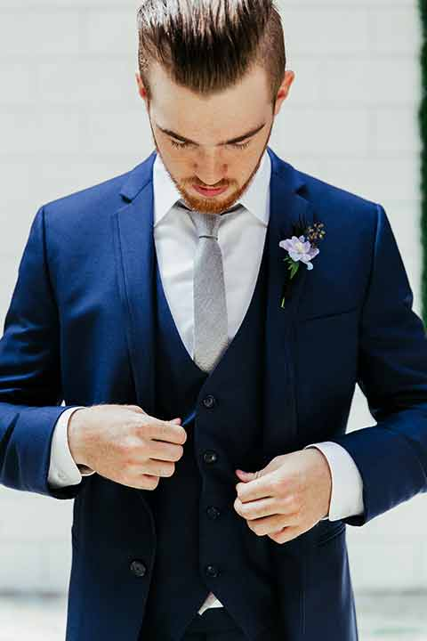 Sandbox-styled-shoot-groom-fastening-buttons-on-suit-groom-wearing-a-blue-suit-and-grey-tie