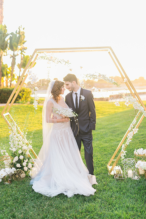 san-diego-styled-shoot-bride-and-groom-ceremony-space-octagon-arch-with-minimal-flowers-bride-in-a-lace-gown-with-sleeves-groom-inan-grey-tuxedo-with-a-black-shawl-lapel